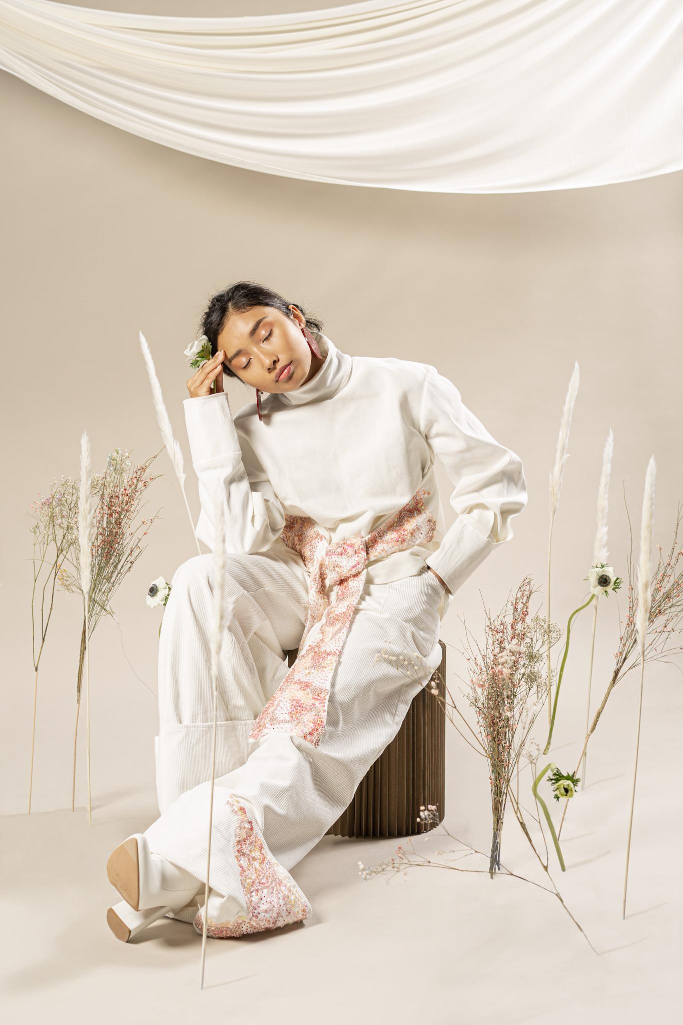 Une femme assise sur un tabouret en carton, entourée de fleurs, tenant une fleur dans sa main droite qui s'appuie du bout des doigts sur son front.