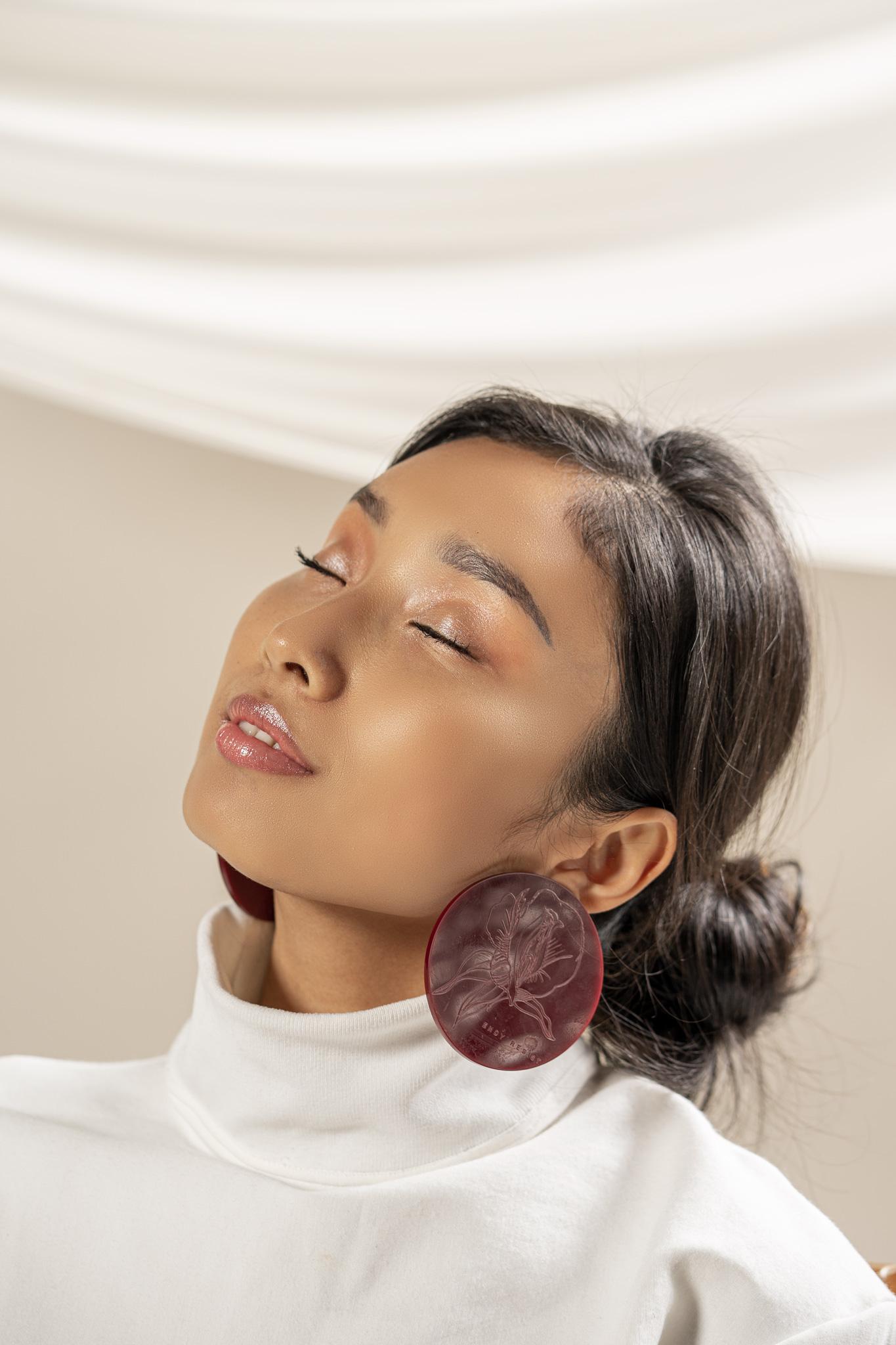 Une femme, assise la tête penchée légèrement en arrière, les yeux fermés, la bouche entrouverte, portant une boucle d'oreille rouge sur un fond beige.
