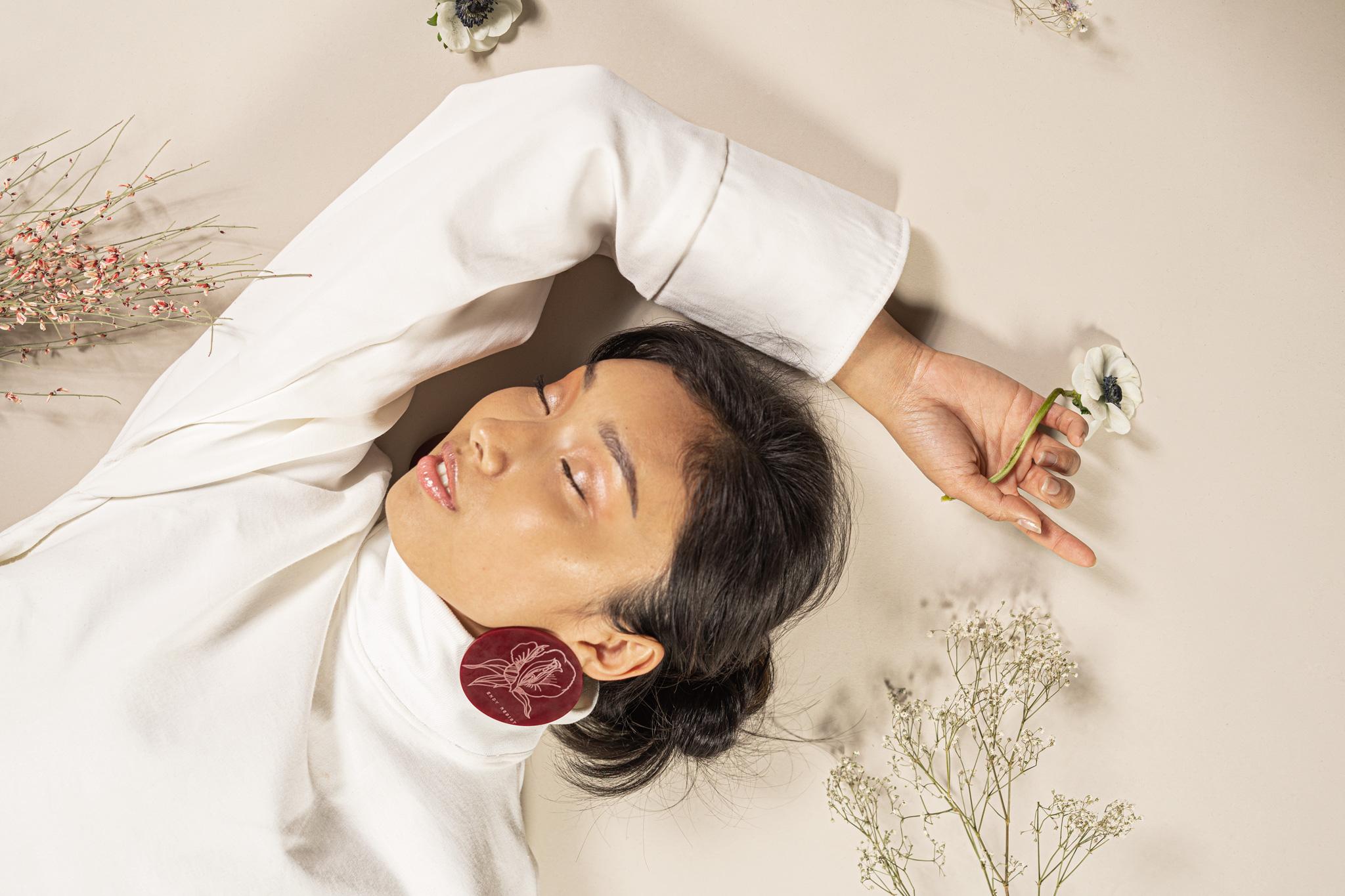 Une femme allongée par terre, un bras au dessus de la tête portant une fleur, les yeux fermés.