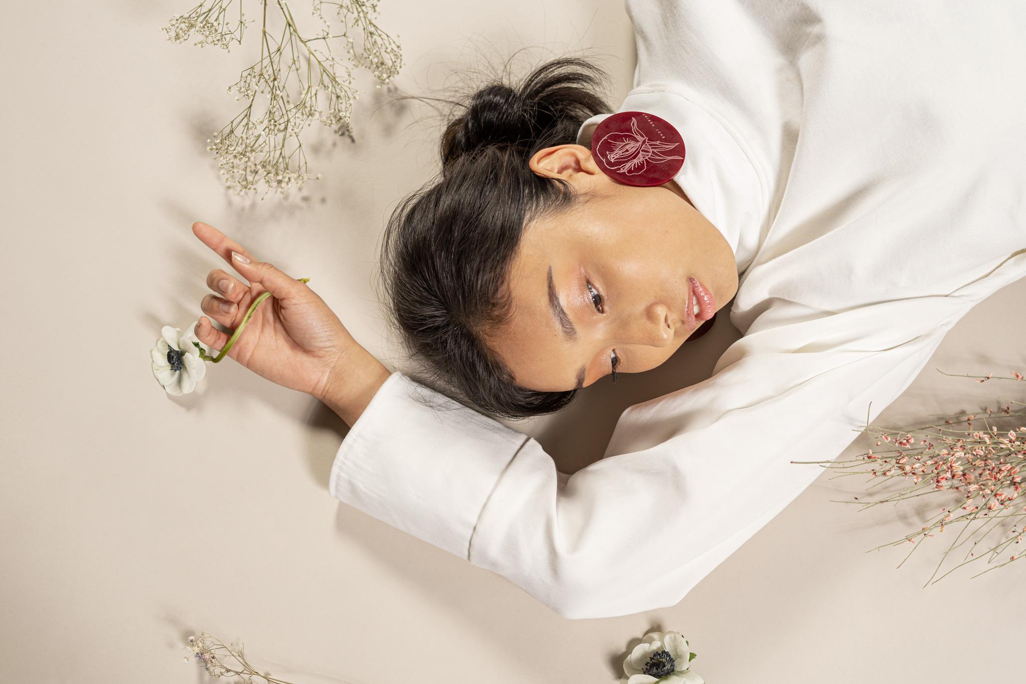 Une femme allongée par terre, un bras au dessus de la tête portant une fleur, regardant au loin.
